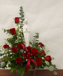 Madonna keepsake statue surrounded by red roses and greenery