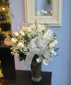White roses and baby's breath in a clear glass vase accented with a silver bow.