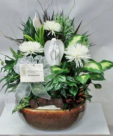 Dish garden of green plants and flowers with an angel keepsake for the garden or home.