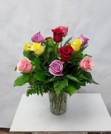 One dozen medium-stemmed roses in assorted colors, arranged in a clear glass vase.