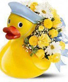 Yellow ceramic duck filled with yellow and white flowers.