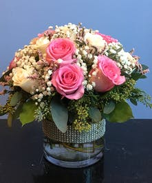 Roses and baby's breath in a bejeweled cylinder vase.