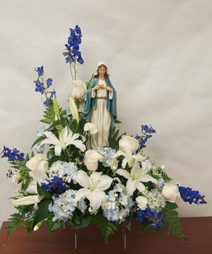 Blue and white flowers surrounding a keepsake Madonna statue