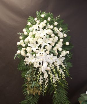 White sympathy spray of roses, lilies and orchids displayed on an easel