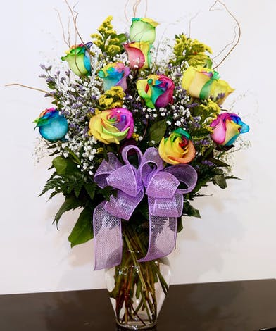Twelve rainbow roses in a clear glass vase.