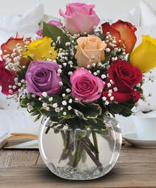 A bubble bowl filled with one dozen roses in assorted colors