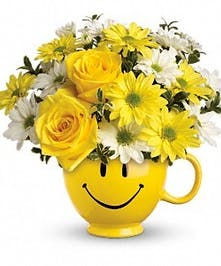 Smiley face mug full of roses and daisies.