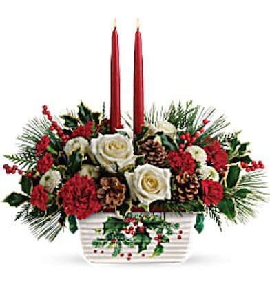 Christmas centerpiece of roses, winter greenery and more in a stoneware dish with two taper candles