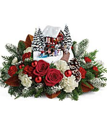 Red roses, white carnations, winter greenery and pine cones beneath a Thomas Kinkade collectible sculpture.