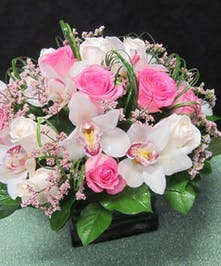 Pink roses and cymbidium orchids in a contemporary cube vase.