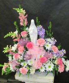 Featuring soft pastels in pink, purple and white with Madonna statue.