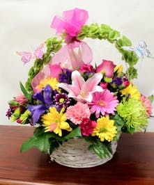 Basket filled with spray roses, carnations, heather and more topped with butterfly decorations.