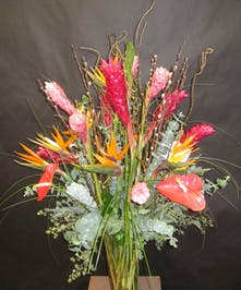 Tall glass vase filled with tropical flowers like red ginger, anthurium and birds of paradise.