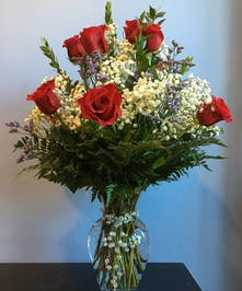 Red roses and baby's breath in a clear glass vase accented with opal beads.
