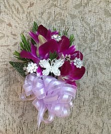 Purple dendrobium orchid wristlet with purple ribbon and crystals.