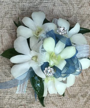 Wristlet made of white dendrobium orchids and blue ribbon.