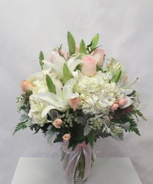 Pastel pink and white flowers with greenery arranged in a clear glass vase tied with pink ribbon