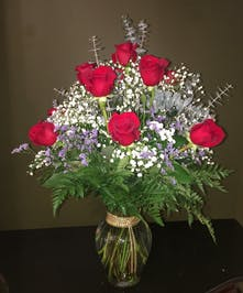 One dozen roses with gold chain roping around the vase