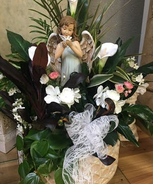 Assorted green and blooming plants in a basket surrounding an angel keepsake for the garden.