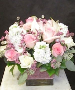 Pink & white flowers in a cube vase with a pink ribbon