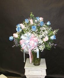 Two dozen roses in light blue and blush pink in a clear glass vase