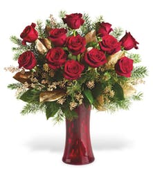 One dozen red roses in a red vase arranged with winter greenery and gold accents
