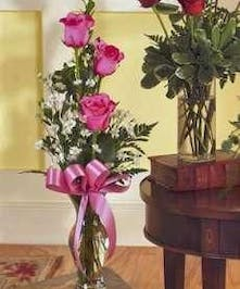 Bud vase filled with three pink roses and assorted greenery