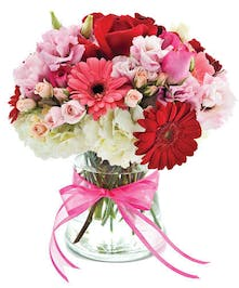 Clear glass vase of roses, spray roses and hydrangeas in reds, pinks and white.