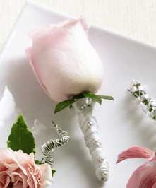 Boutonniere featuring a pink rose and wrapped stem.