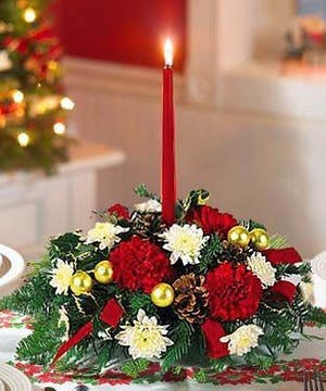 Christmas centerpiece of red and white flowers, gold ornaments and red taper candles