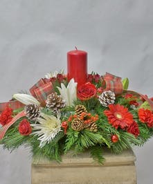 Christmas centerpiece featuring red and white flowers, winter greenery and a red pillar candle.
