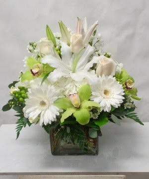 White daisies and green cymbidium orchids in a clear glass cube vase.
