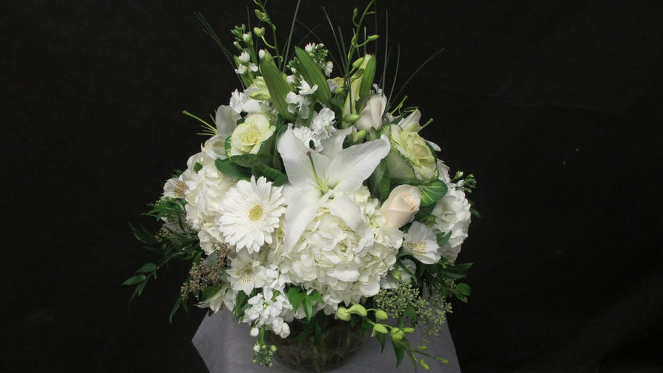 Winter bouquet of all-white flowers and greenery in a clear glass vase.