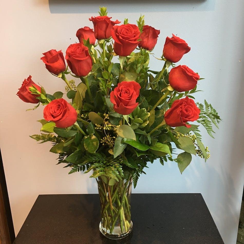 Twelve long-stemmed premium roses accented with deluxe greens in a simple sleek vase.
